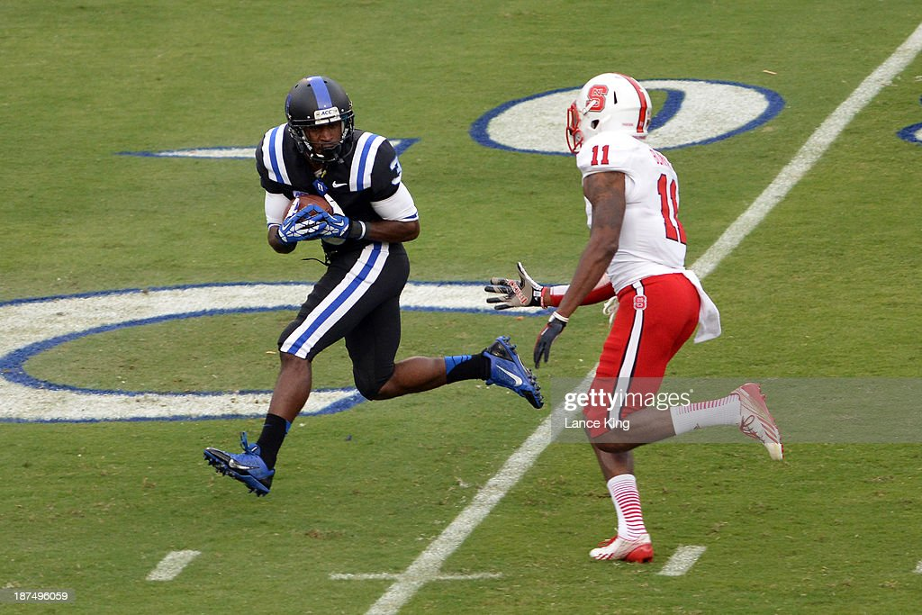 Jamison Crowder #3 of the Duke Blue Devils catches a pass against Juston Burris #11 of the North Carolina State Wolfpack at Wallace Wade Stadium on November 9, 2013 in Durham, North Carolina.