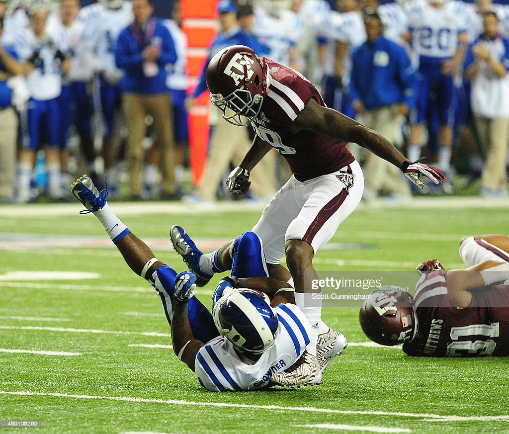 Jamison Crowder of the Duke Blue Devils is tackled by Deshazor Everett of the Texas AM Aggies during the ChickFilA Bowl at the Georgia Dome on...