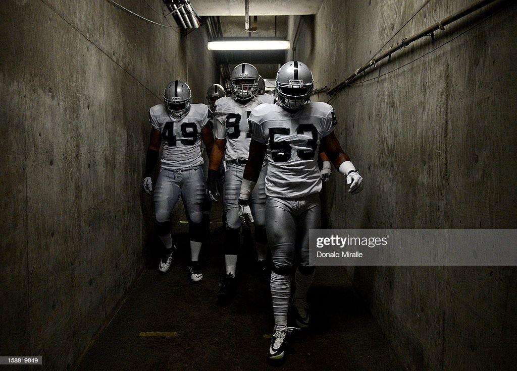 Jamiza Olawale #49, Jack Crawford #91and Omar Gaither #53 of the Oakland Raiders walk down the tunnel before the game against the San Diego Chargers on December 30, 2012 at Qualcomm Stadium in San Diego, California.