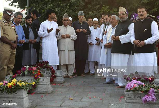 Jammu and Kashmir Chief Minister Omar Abdullah with other leaders prays after laying wreath on the graves at MazareShohda during a ceremony marking...