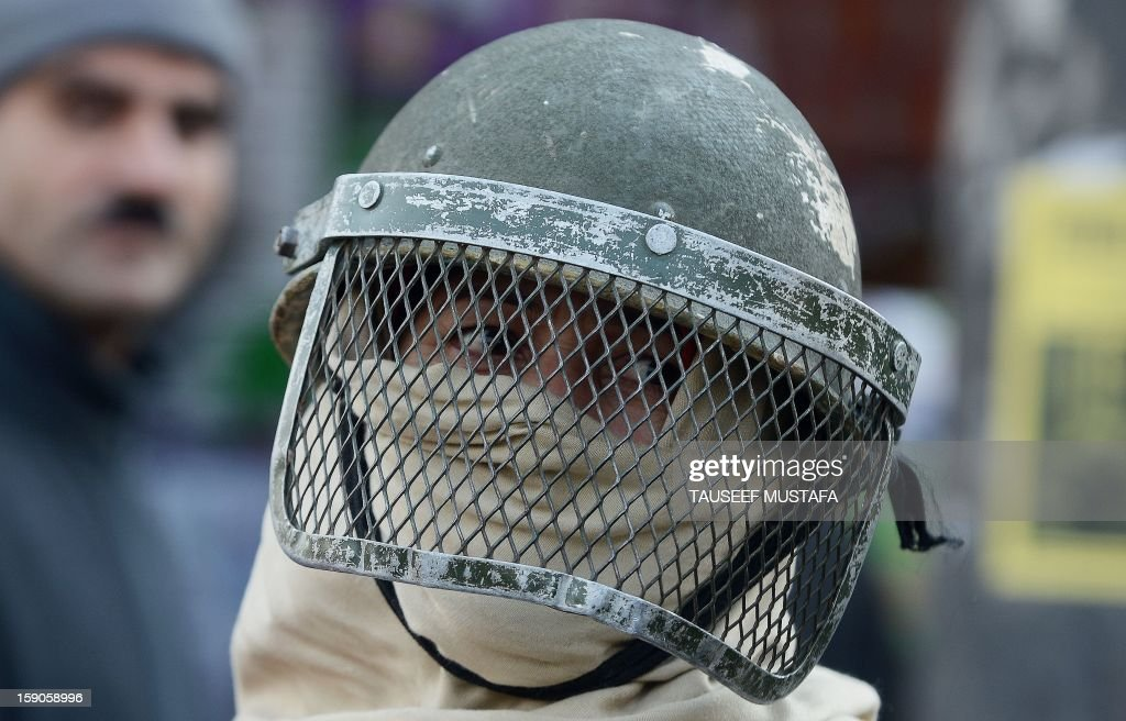 A Jammu and Kashmir female police officer looks on during a protest against a court verdict sentencing two Kashmiris to life imprisonment in Srinagar on January 7, 2013. The Muslim-majority region is in the grip of a 20-year insurgency against rule from New Delhi, which has left more than 47,000 people dead by the official count, a separatists put the toll twice as high. AFP PHOTO/ Tauseef MUSTAFA