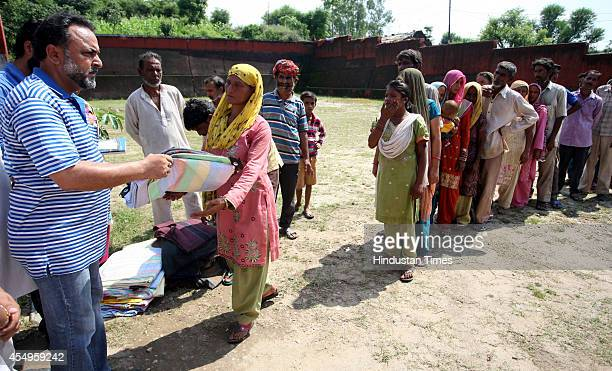 Jammu and Kashmir government officer providing blankets and other useable items to flash flood victims at Majheen village on September 8 2014 about...