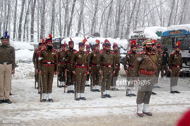 Jammu and Kashmir Police Force soldiers stand amid Snowfall at a flag raising ceremony during Republic Day celebrations in Sopore area of North...