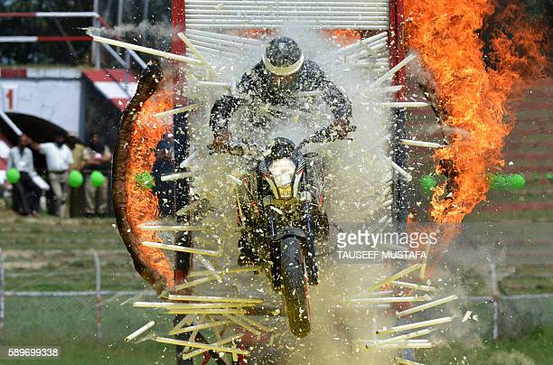 Jammu and Kashmir Police motorcyclist rides through a burning hoop and a wall of glass tubes during an Independence Day event at The Bakshi Stadium...