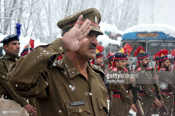 Jammu and Kashmir police officer salutes amid snowfall at Police Lines in sopore during the republic day celebrations The 68th Republic Day...
