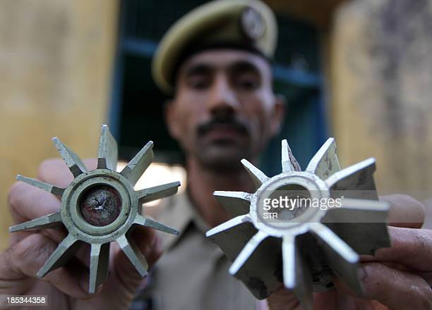 A Jammu and Kashmir policeman displays mortar shrapnel at a home in Najwal village in Pargwal sector of Akhnoor district about 40 kms from Jammu on...
