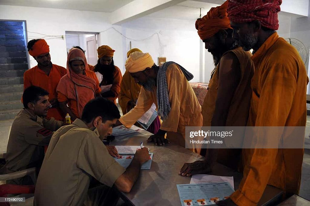 A Jammu and Kashmir policeman fills the registration form of a Hindu holy man for Amarnath Yatra registration for the annual pilgrimage to the Amarnath cave shrine on July 2, 2013 in Jammu, India. Thousands of pilgrims annually visit the remote Himalayan shrine of Amarnath at 3,888 meters (12,756 feet) above sea level to worship an icy stalagmite representing Shiva, the Hindu god of destruction. A small batch of 1,785 devotees today left Jammu base camp for the Amarnath cave shrine. The sixth batch, including 1,395 male, 326 women and 14 children, apart from 50 sadhus, was on its way to twin base camps of Pahalagam and Baltal in Kashmir Valley. Over 50,000 pilgrims have paid obeisance at the cave shrine of Amarnath in south Kashmir till last evening.