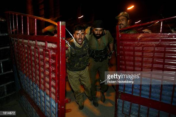 A Jammu and Kashmir policeman helps his colleague to an ambulance following a grenade attack on a police barracks September 21 2002 in Srinagar India...