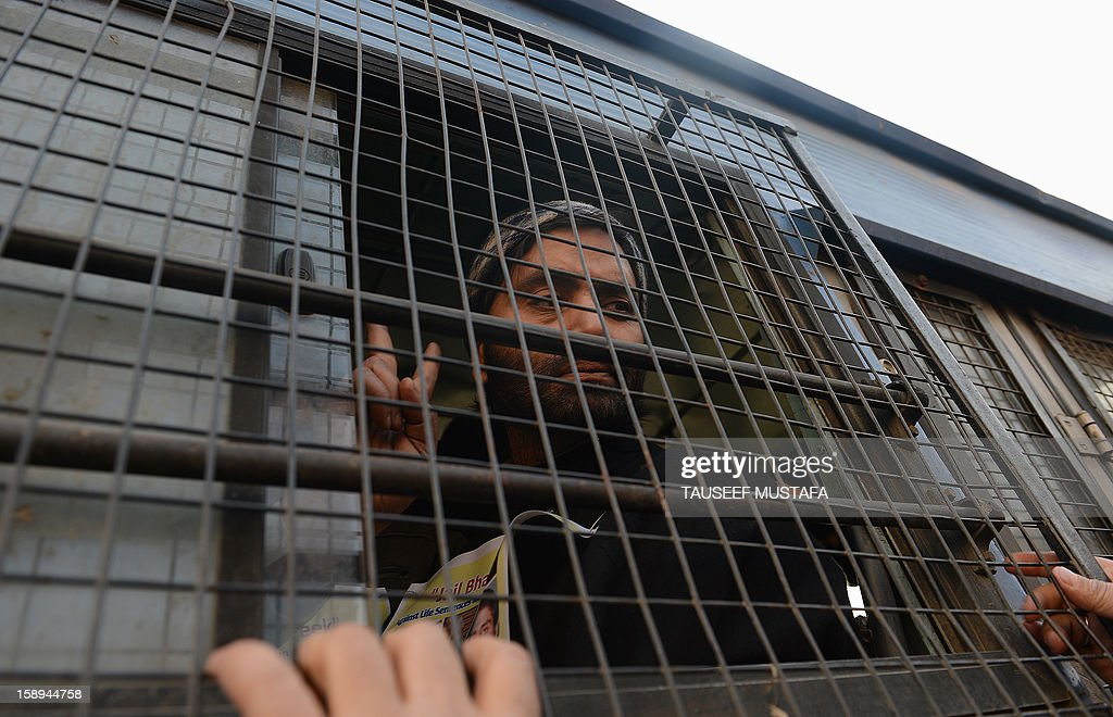 Jammu Kashmir Liberation Front (JKLF) chairman Yasin Malik gestures inside a police vehicle during a protest against a court verdict sentencing two Kashmiris to life imprisonment in Srinagar on January 4, 2013. The Muslim-majority region is in the grip of a 20-year insurgency against rule from New Delhi, which has left more than 47,000 people dead by the official count, a separatists put the toll twice as high. AFP PHOTO/ Tauseef MUSTAFA
