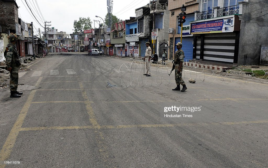Jammu & Kashmir police personnel spread barbed wires on road and keep tight vigil during a curfew on August 12, 2013 in Jammu, India. Authorities imposed curfews in seven towns in the Indian portion of Kashmir on Sunday as sporadic clashes between Hindus and Muslims continued for a third day, officials said. Jammu and Kashmir's Home Minister Sajjad Ahmad Kichloo tendered his resignation today amid widespread communal violence in Kishtawar district. Kichloo said his consciousness didn't allow him to head the police department since J&K Chief Minister Omar Abdullah had ordered a judicial probe into the clashes.