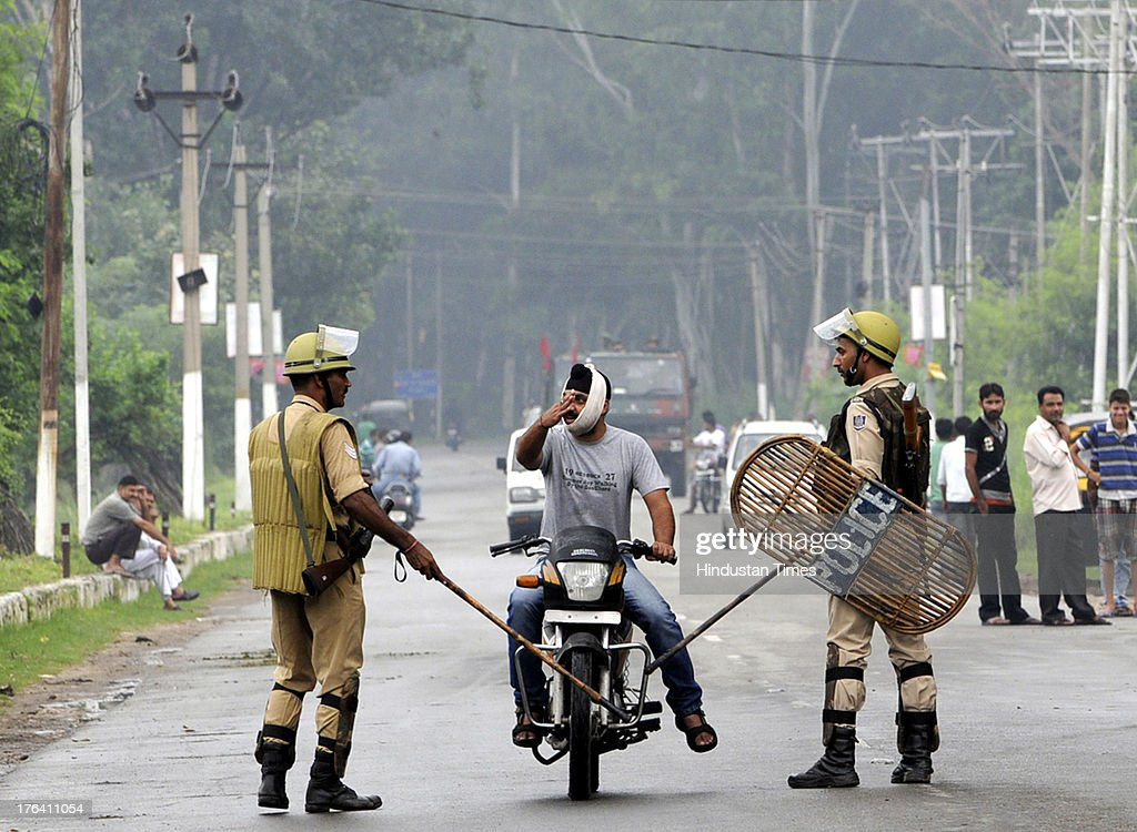 Jammu & Kashmir Police personnel stop a commuter on a motorbike during a curfew on August 12, 2013 in Jammu, India. Authorities imposed curfews in seven towns in the Indian portion of Kashmir on Sunday as sporadic clashes between Hindus and Muslims continued for a third day, officials said. Jammu and Kashmir's Home Minister Sajjad Ahmad Kichloo tendered his resignation today amid widespread communal violence in Kishtawar district. Kichloo said his consciousness didn't allow him to head the police department since J&K Chief Minister Omar Abdullah had ordered a judicial probe into the clashes.