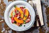 Ham jamon serrano prosciutto, melon and arugula salad on grey plate on vintage background. Top view