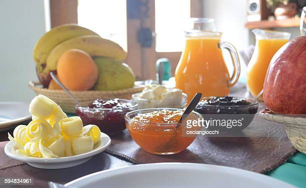 Jams, fruit, juice and butter on breakfast table