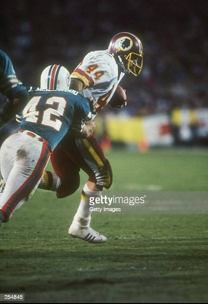 Defensive lineman Lyle Blackwood of the Miami Dophins lunges at running back John Riggins of the Washington Redskins during the Super Bowl XVII at...