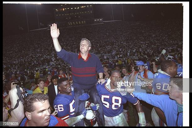 New York Giants head coach Bill Parcells is paraded around on the shoulders of players Lawrence Taylor and Carl Banks after winning Super Bowl XXV...