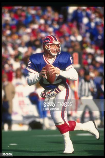 Quarterback Jim Kelly of the Buffalo Bills looks to pass the ball during a playoff game against the Denver Broncos at Rich Stadium in Orchard Park...