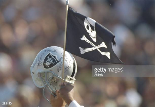 A Los Angeles Raiders fan waves a helmet and flag during a playoff game against the Denver Broncos at the Los Angeles Memorial Coliseum in Los...