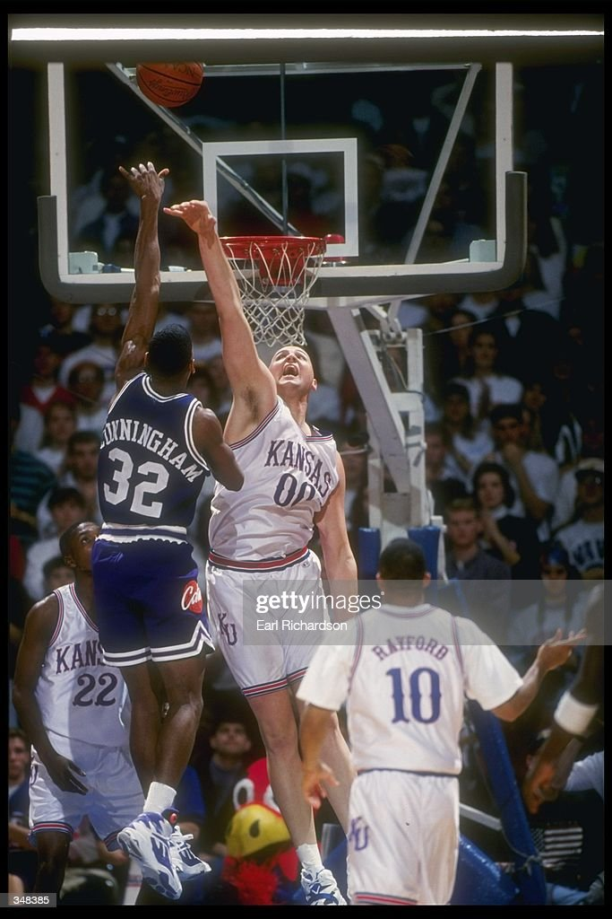 Center Greg Ostertag of the University of Kansas tries to block a shot from Deryl Cunningham of Kansas State during the Kansas Jayhawks 6864 loss to...