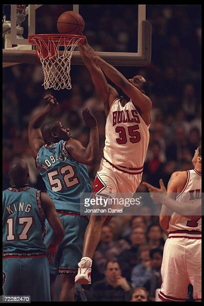Forward Jason Caffrey of the Chicago Bulls drops the ball into the hoop above defending center Eric Mobley of the Vancouver Grizzlies at the United...