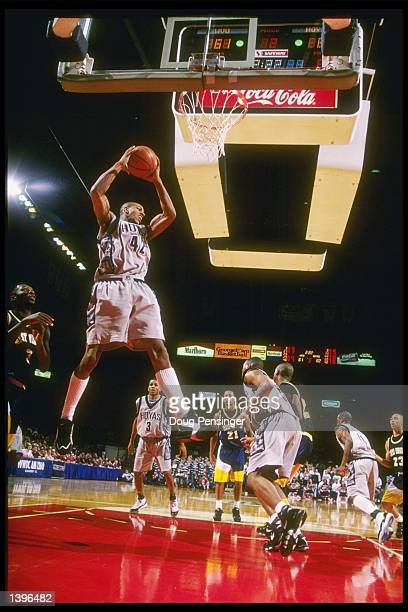 Foward Jerome Williams of the Georgetown Hoyas grabs the rebound as guard Allen Iverson of the Hoyas and guard Jarrod West of the West Virginia...