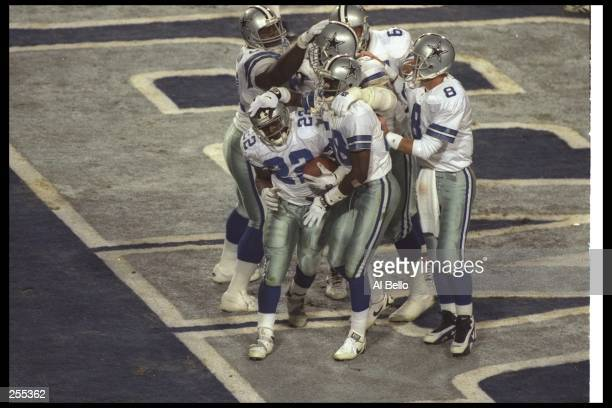 Running back Emmitt Smith of the Dallas Cowboys celebrates with teammates Michael Irvin and Troy Aikman after Smith scored a fourth quarter touchdown...