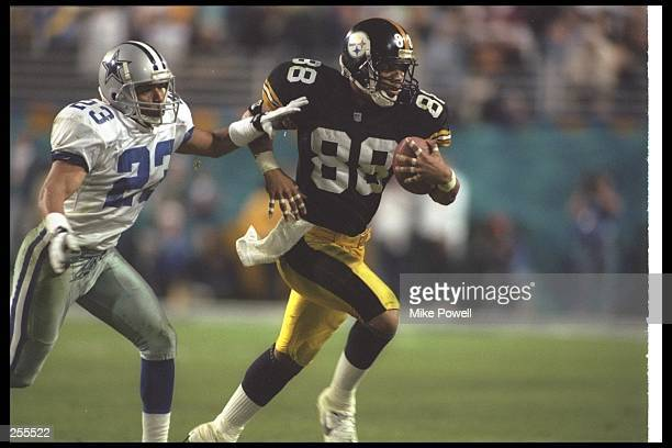 Wide receiver Andre Hastings of the Pittsburgh Steelers runs down the field as cornerback Robert Bailey of the Dallas Cowboys chases after him at...