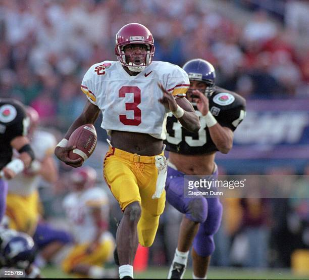 Wide receiver Keyshawn Johnson of the USC Trojans runs downfield while bing pursued by strong safety Eric Collier of the Northwestern Wildcats during...