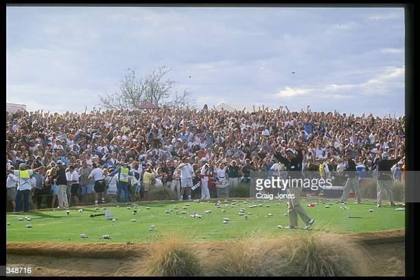 Fans throw beer onto the course in celebration as Tiger Woods makes a hole in one during the Phoenix Open at the TPC of Scottsdale in Scottsdale...