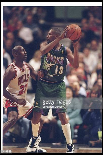 Forward Glenn Robinson of the Milwaukee Bucks looks to pass the ball as Chicago Bulls guard Michael Jordan covers him during a game at the United...