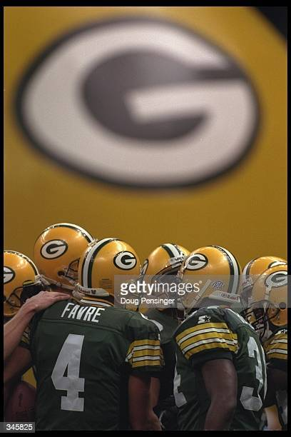 Quarterback Brett Favre of the Green Bay Packers talks to a group of his teammates in front of a giant Green Bay logo in the background as the...