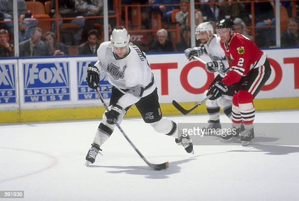 Luc Robitaille of the Los Angeles Kings is pursued by Eric Weinrich of the Chicago Blackhawks during a game at the Great Western Forum in Inglewood...