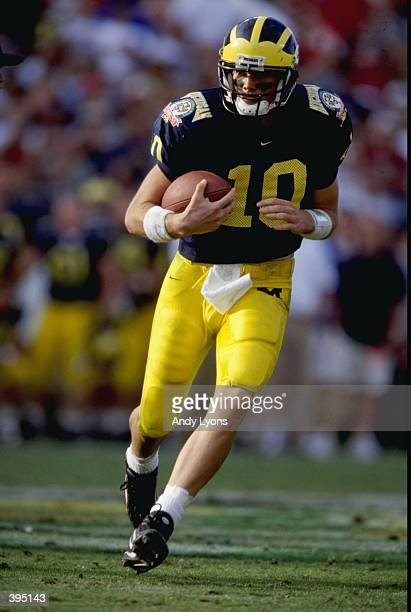 Tom Brady of the Michigan Wolverines carries the ball during the Citrus Bowl against the Arkansas Razorbacks at the Florida Citrus Bowl in Orlando...