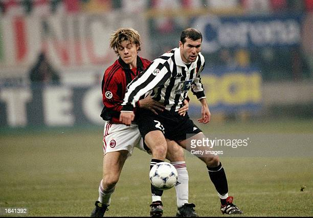 Zinedine Zidane of Juventus is challenged by Thomas Helveg of AC Milan during the Italian Serie A match at the San Siro Stadium in Milan Italy The...