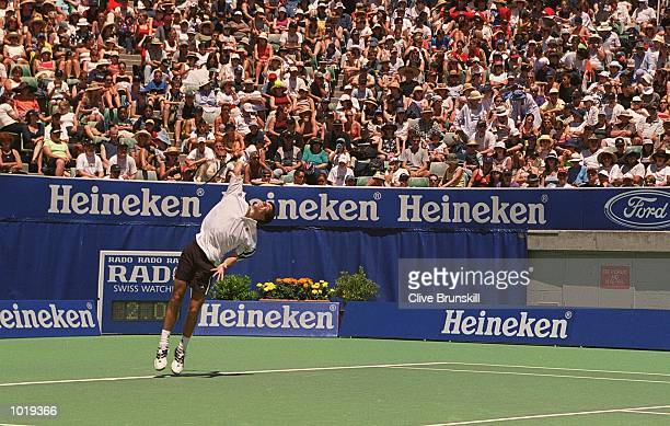 A large crowd watches Tim Henman of Great Britain serve in his match against Jerome Goldmard of France during his first round match during the day...