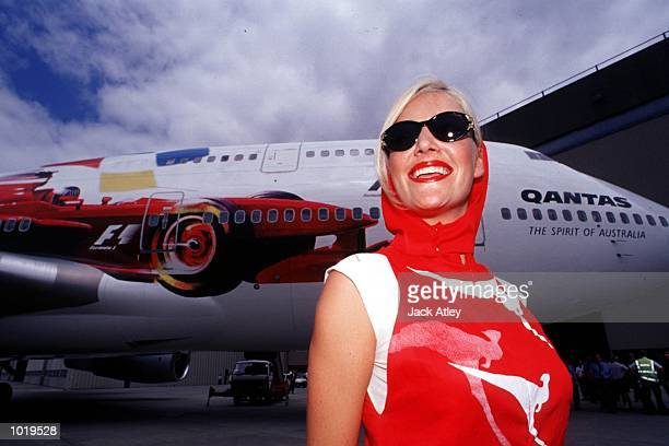 New pit girl uniforms showing the Qantas logo are modelled in front of a 747 Qantas plane showing a formula 1 car painted on the side at the Qantas...