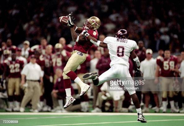 Peter Warrick of the Florida State Seminoles jumps and catches the ball as Anthony Midget of the Virginia Tech Hokies gaurds him during the Nokita...