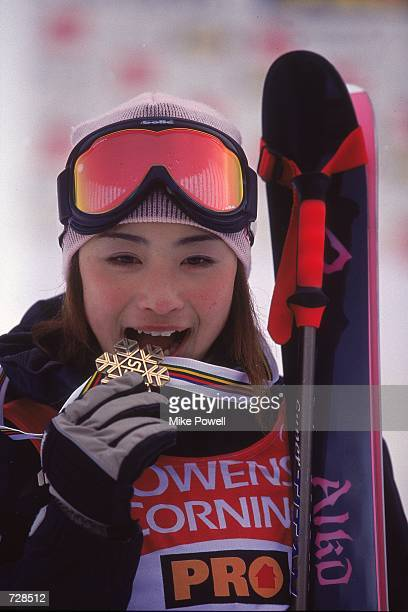Akio Uemura of Japan playfully tries to bite her medal during the Mogul Finals for the World Freestyle Ski Championships in Whistler British Columbia...