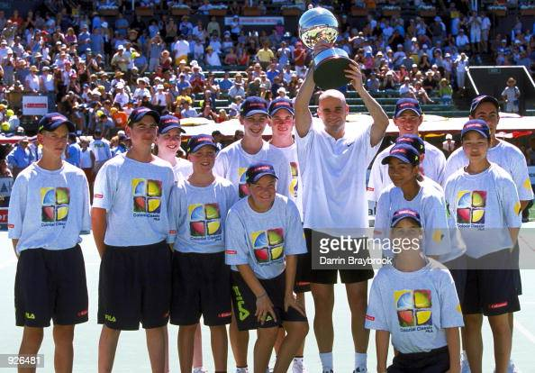 Andre Agassi from the USA holds the Colonial Classic trophy above his head and poses with the ballgirls and ballboys after winning the final against...