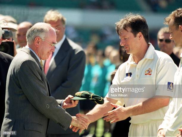 Australian Prime Minister John Howard presents Australian captain Steve Waugh with a commmorative cap to to celebrate 100 years of Australian...