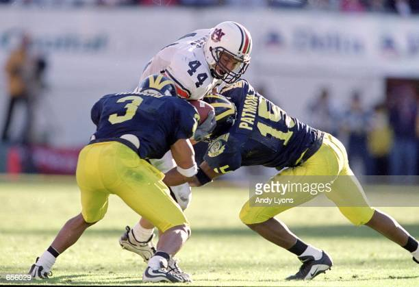 Heath Evans of the Auburn Tigers carries the ball as he is tackled by Todd Howard and Travis Demeester of the Michigan Wolverines during the Citrus...