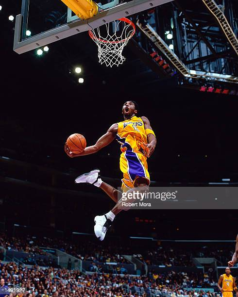 Kobe Bryant of the Los Angeles Lakers soars to the basket for a slam dunk against the Houston Rockets during their NBA Game at Staples Center in Los...