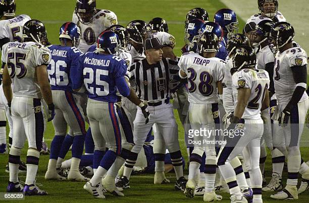 Line Judge Walt Anderson breaks up a scuffle between the New York Giants and the Baltimore Ravens during Super Bowl XXXV at Raymond James Stadium in...