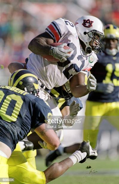 Rudi Johnson of the Auburn Tigers runs with the ball as Norman Boebert of the Michigan Wolverines moves to tackle him during the Citrus Bowl Game at...