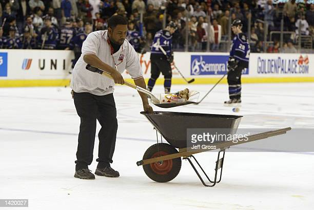 A maintenance worker picks up trash thrown onto the ice by fans who were upset with a call made by referee Mike Hasenfrantz during a game between the...