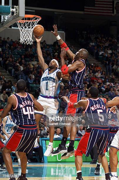 Baron Davis of the Charlotte Hornets goes to the basket against Walt Williams of the Houston Rockets during their game at the Charlotte Colesium in...