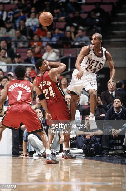 Forward Richard Jefferson of the New Jersey Nets passes over guard Jim Jackson of the Miami Heat during the NBA game at Continental Airlines Arena in...