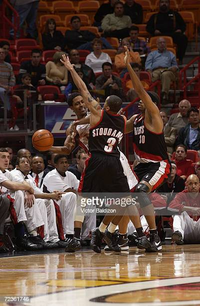 Point guard Rod Strickland of the Miami Heat passes around point guard Damon Stoudamire of the Portland Trail Blazers during the NBA game at American...