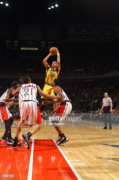 Reggie Miller the Indiana Pacers puts up a long jump shot between Walt Williams Kenny Thomas and Cuttino Mobley of the Houston Rockets at the Compaq...