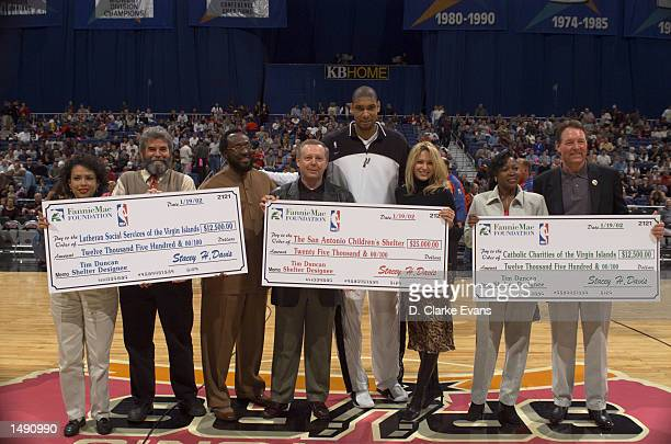Tim Duncan of the San Antonio Spurs and his wife Amy donate $50 which Duncan was awarded with by the Fannie Mae Foundation and the NBA for being...