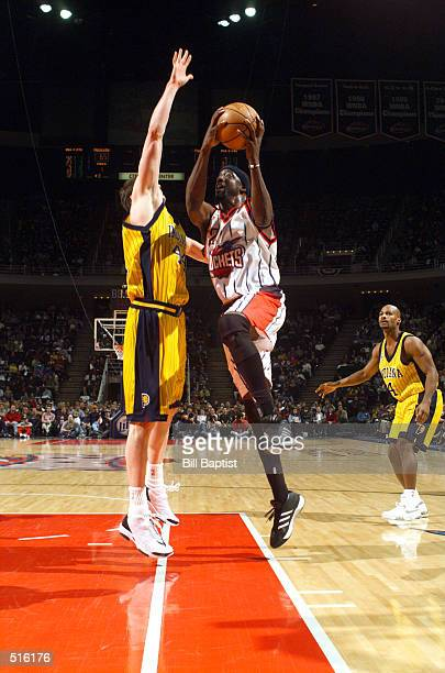 Walt Williams of the Houston Rockets drives to the basket while being defended by Austin Croshere of the Indiana Pacers at the Compaq Center in...